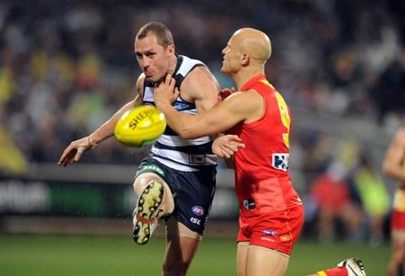 James Kelly of Geelong kicks the ball as he's tackled by Gary Ablett of Gold Coast Suns, during the Round 10 AFL match between the Geelong Cats and the Gold Coast Suns at Simonds Stadium in Geelong, Saturday, June 1, 2013. (AAP Image/Joe Castro)