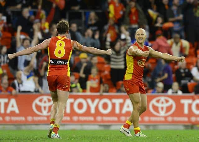Suns players Luke Russell (left) and Gary Ablett react following the Round 17 AFL match between the Gold Coast Suns and the Collingwood Magpies at Metricon Stadium on the Gold Coast, Saturday, July 20, 2013. (AAP Image/Dave Hunt) NO ARCHIVING, EDITORIAL U