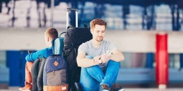Stock image of two travellers with mobile phones waiting at the airport departure area for their delay flight.