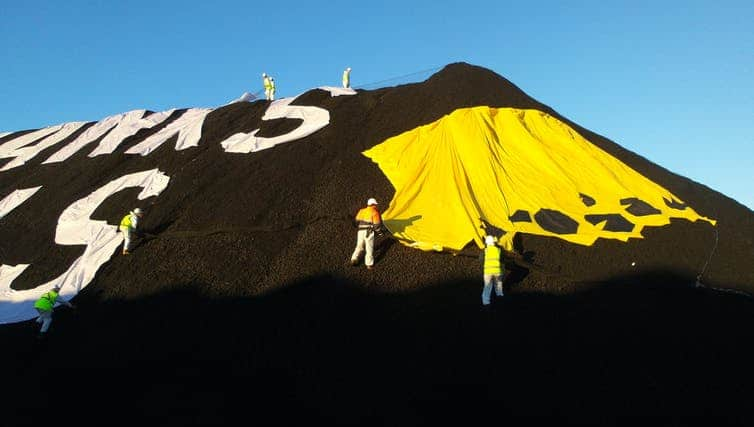 Greenpeace members protesting at Newcastle port in 2017, calling on the Commonwealth Bank to stop investing in coal. (Jaz Kaelin/The Conversation)