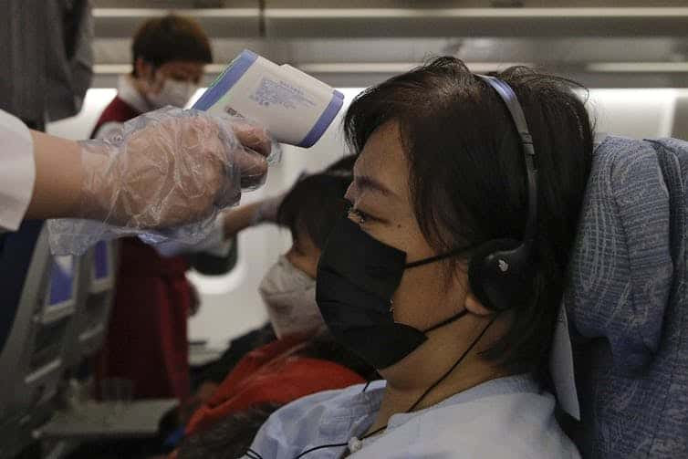 Flight attendants check temperatures of passengers aboard an Air China flight from Melbourne to Beijing on Feb. 4, 2020.         AP Photo/Andy Wong/The Conversation
