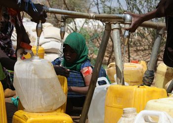Newly arrived refugees collect water at an Oxfam tap stand in Africa. Photo: Anna Ridout/Oxfam