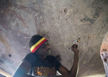Traditional owner, Ian Waina, recording the estimated 17,300 year old painting of a kangaroo found in a hard-to-access rock cluster in the northeast Kimberley region. Image: Peter Veth, Balanggarra Aboriginal Corporation