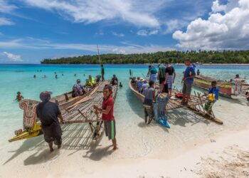 Tourists and locals with canoes on a Papua New Guinea beach. Image by Sally Wilson from Pixabay