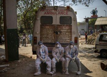 Exhausted crematorium workers sit on an ambulance in New Delhi, India, Saturday, April 24 2021. Photo: AP Photo/Altaf Qadri.