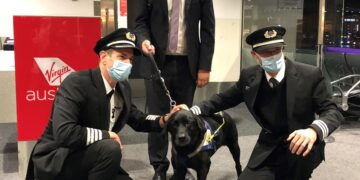 Odie and owner Chris Edwards with members of the crew on his final flight