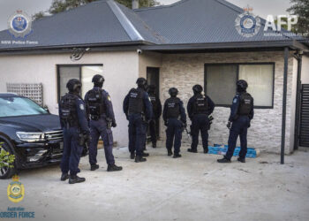 Officers prepare to search one of the properties last week. Photo credit: AFP